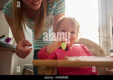 Kleinkind sitzen im Hochstuhl, Mahlzeit, Mutter hinter ihr stehen - Stockfoto
