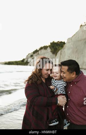 Mutter und Vater am Strand mit kleinen Jungen auf Arm, Toronto, Ontario, Kanada - Stockfoto