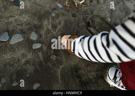 Ansicht des kleinen Jungen am Strand Kieselsteine Abholung beschnitten - Stockfoto
