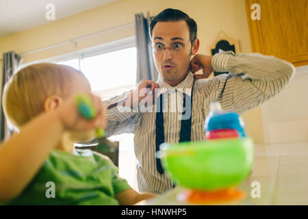 Vater und seinem kleinen Sohn in Küche, Vater Krawatte anziehen, während Sohn frühstückt - Stockfoto