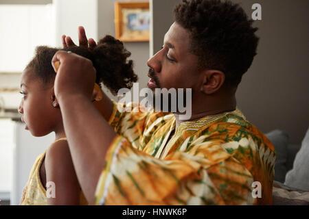 Mann Haare Bürsten Tochter im Wohnzimmer - Stockfoto