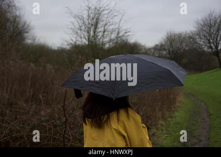 Ein Mädchen in einem gelben Regenmantel hält einen schwarzen Regenschirm im Regen in einem Feld - Stockfoto