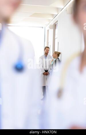 Über Schulter Blick auf männlichen Arzt und Frau, die Diskussion im Krankenhausflur - Stockfoto