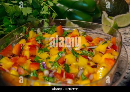 Frisch zubereitetes Mango Salsa in Kunststoffbehälter, in einer häuslichen Küche mit Limonen und Koriander. - Stockfoto