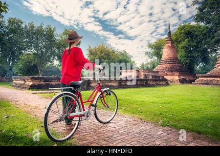 Frau im roten t-Shirt mit Vintage Fahrrad Blick auf alte ruiniert buddhistischer Tempel in erstaunliche Sukhothai - Stockfoto