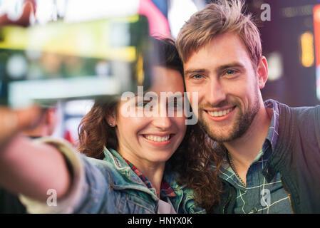 Junges Paar nehmen Selfie in beleuchteten Stadt Straße - Stockfoto