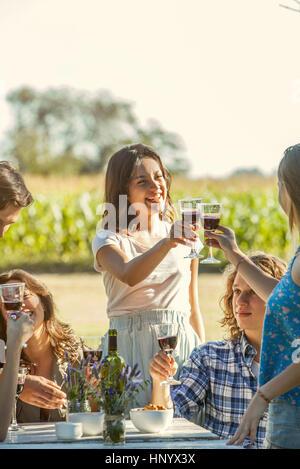 Freunde, die Gläser klirren, und genießen Sie Wein im freien - Stockfoto