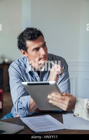 Man hören, wie Kollege ihm etwas auf einem digitalen Tablet zeigt - Stockfoto