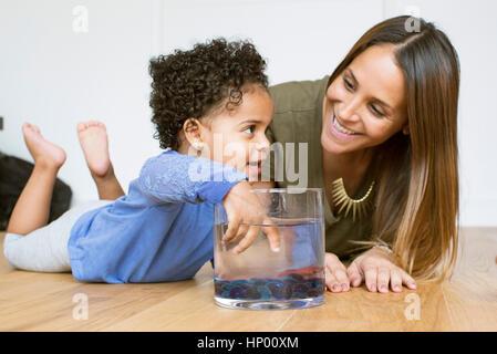 Mutter und Kleinkind Tochter spielt mit Goldfisch - Stockfoto
