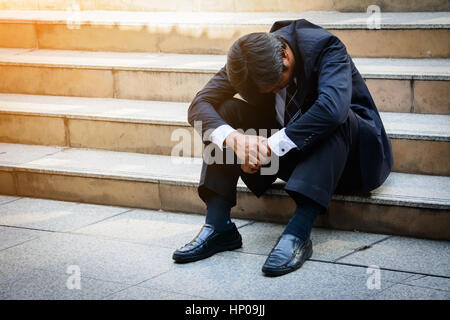 Betonte Geschäftsmann an Treppe im Freien sitzen. Konkurs Geschäftsmann im Freien zu sitzen. - Stockfoto