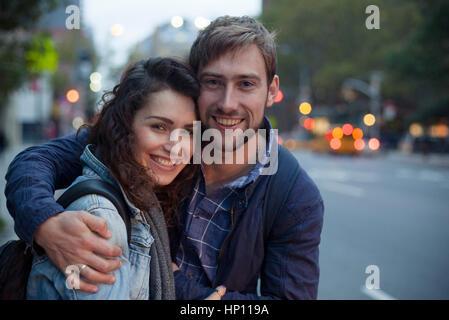 Junges Paar umarmt auf Stadtstraße in der Nacht, Porträt - Stockfoto