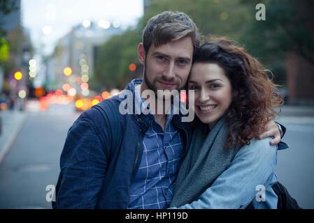 Paar auf Stadtstraße abends, Porträt - Stockfoto