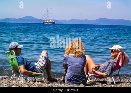 Familie am Meer beobachten das Boot unter der heißen Sonne, Sicak Günes Altinda Deniz Kenarinda Oturan aile - Stockfoto