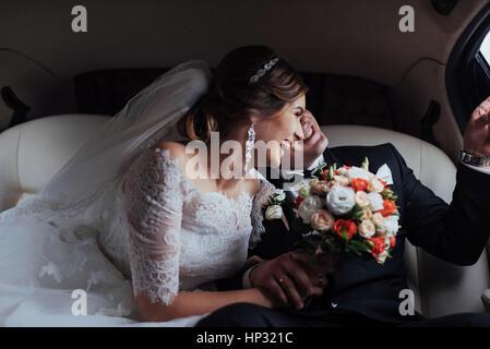 junges Paar in einem Auto in Hochzeitstag. - Stockfoto