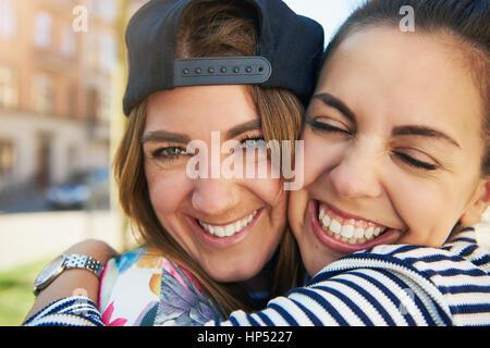 Zwei liebende junge Frauen posiert in einer liebevollen Umarmung mit strahlenden glückliche Lächeln der Zufriedenheit, - Stockfoto