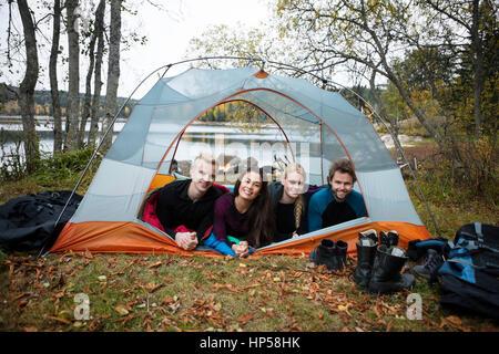 Lächelnden jungen Freunde liegen im Zelt am Seeufer - Stockfoto