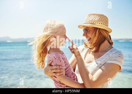 Junge weibliche in hat Holding kleines Mädchen auf Händen und mit ihr spielen auf dem Hintergrund von Meer. - Stockfoto