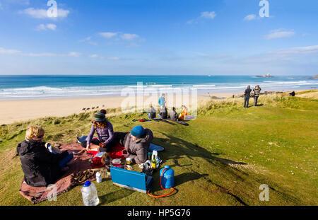 Ein Familienpicknick auf einem Felsen in der Sonne nach einem Surf in der salzigen. - Stockfoto