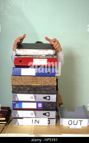 Geschäftsmann, versteckt hinter riesigen Wust von Papieren im Büro - Stockfoto