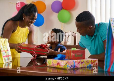 Glückliche schwarze Familie zu Hause. African american Vater, Mutter und Kind feiert Geburtstag, Spaß an der Partei. - Stockfoto