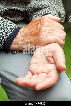 Eine ältere Frau ihren schmerzlichen Handgelenk Holding - Stockfoto
