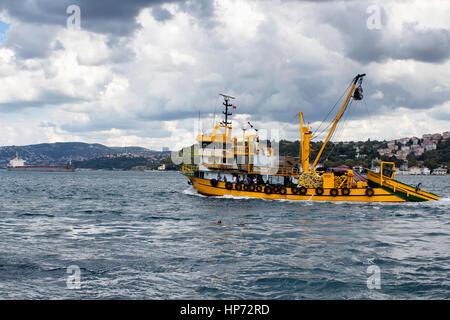 Große, gelbe Fischerboot und Fischer darauf kreuzt Bosporus in Istanbul. Großer Frachter ist im Hintergrund. Es - Stockfoto