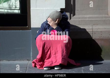 Gesicht versteckt intelligenter junger Mann auf Glasgow Straße Bettler betteln um Geld betteln mit Schale rosa Decke - Stockfoto