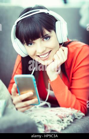 Junge lächelnde Frau mit Kopfhörern auf dem Sofa entspannen und anhören von Musik online über ein smartphone - Stockfoto