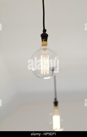 Ein modernes Edison style LED Glühbirne hängt von einer weissen Decke - Stockfoto