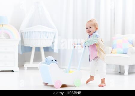 Baby Boy mit hölzernen Push Walker in weiße Schlafzimmer mit Pastell Regenbogen Farbe Spielzeug laufen lernen. Spielzeug - Stockfoto