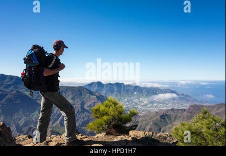 Ältere männliche Wanderer auf Alta Vista Berg auf Gran Canaria mit La Aldea de San Nicolas Dorf in Ferne. Kanarischen Inseln. Spanien