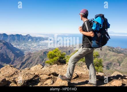 Ältere männliche Wanderer auf Alta Vista Berg auf Gran Canaria mit La Aldea de San Nicolas Dorf in Ferne. Kanarischen - Stockfoto