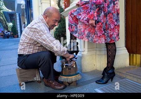 Shoeshine Mann und Client in Nuruosmaniye Straße, Istanbul, Türkei - Stockfoto