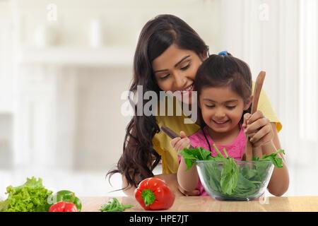 Lächelndes Mädchen mit ihrer Mutter machen Gemüsesalat - Stockfoto
