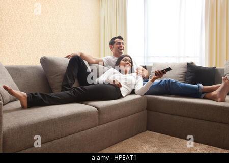 Lächelnde paar auf Sofa vor dem Fernseher sitzen - Stockfoto