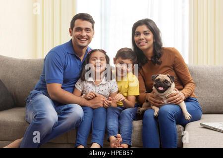 Eltern mit Sohn und Tochter auf Sofa mit Mops - Stockfoto
