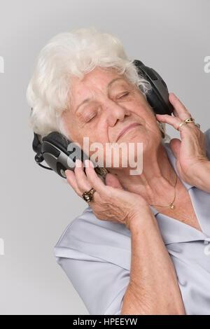 Model Release, Seniorin Mit Kopfhoerer Hoert Musik - ältere Frau anhören von Musik - Stockfoto