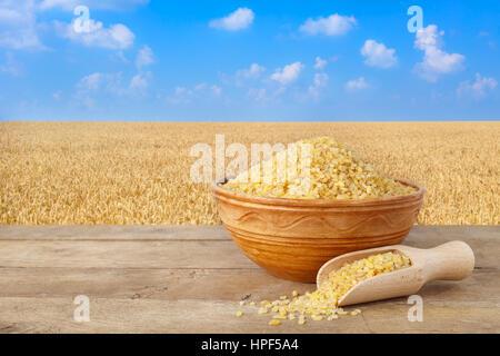 Bulgur oder Couscous in Schüssel geben. Weizenkörner in Sack. Bulgur in Keramikschale auf Tisch mit Feld Weizen - Stockfoto