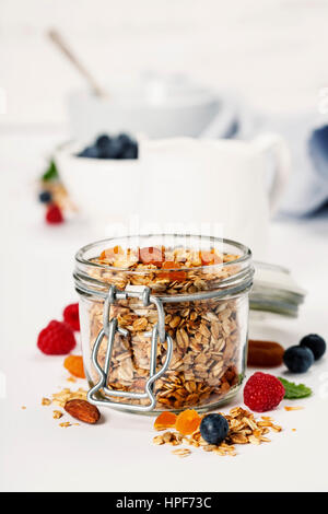 Hausgemachtem Müsli (mit getrockneten Früchten und Nüssen) und gesundes Frühstückszutaten - Honig, Milch und Beeren - Stockfoto