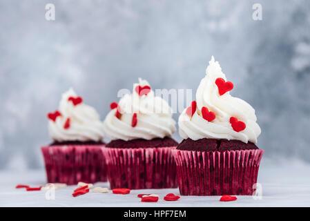 Red Velvet Cupcakes mit Buttercreme frosting und verziert mit Herzen geformt Streuseln. - Stockfoto