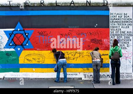 East Side Gallery.writing Mensages in der Wand auf einer Zeichnung von Sternen Juden und die deutsche Flagge. Berlin. - Stockfoto