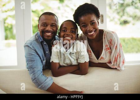 Porträt von Eltern und Sohn beugte sich über Sofa im Wohnzimmer zu Hause - Stockfoto