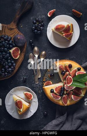 Käsekuchen mit frischen Früchten (Feigen und Trauben) verziert. Ansicht von oben flach legen. Essen Stilleben - Stockfoto