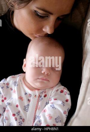 Junge Mutter und ihr Baby schlafen kuscheln - Stockfoto