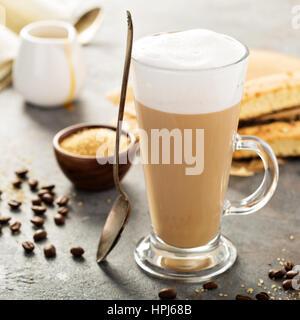 Heißen Kaffee Latte mit braunem Zucker und Biscotti Kekse in Longdrinkglas - Stockfoto