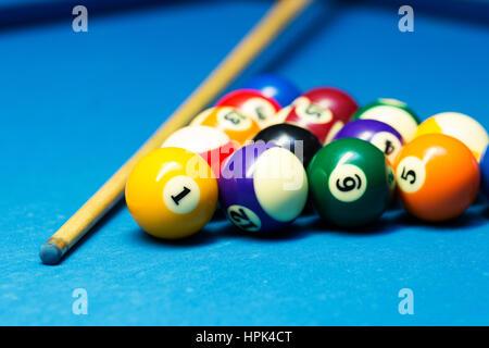 Pool-Billard-Kugeln und Cue auf dem blauen Tuch Tisch - Stockfoto