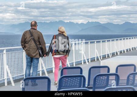 Ein paar, allein auf dem Deck der Fähre, an den Händen halten und den Blick auf die Strait Of Georgia, Bowen Island, - Stockfoto