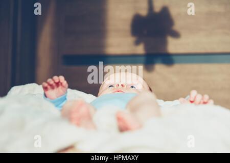 Kleiner Junge im Bett unter Schatten des Spielzeugs. - Stockfoto