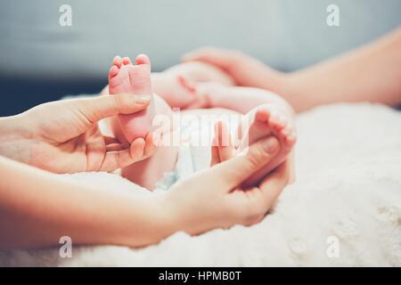 Hauch von der übergeordneten Liebe. Paar streicheln ihr kleines Baby im Bett. - Stockfoto