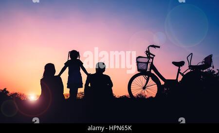 Glückliche Familie, Vater, Mutter und Tochter mit dem Fahrrad bei Sonnenuntergang - Stockfoto